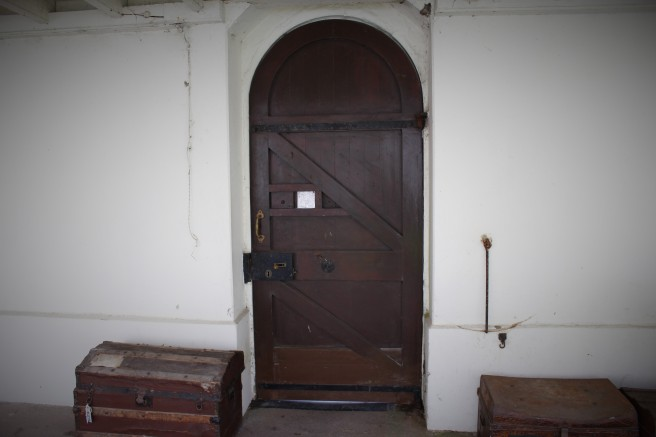 entrance to the convent with grille in the door. old trunks.